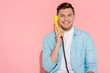 man talking on yellow vintage telephone with pink background