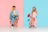 beautiful couple sitting and having conversation on vintage telephones with pink and blue background - 238171093