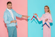 smiling man pointing with finger at woman and choosing empty clothes hangers on pink and blue background