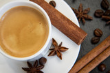 Coffee set. Espresso drink in white cup with cinnamon quills and star anise