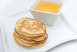 Pancakes and honey. In white porcelain plates