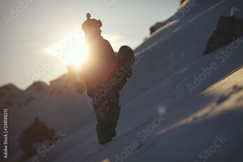 obraz lub plakat Silhouette of snowboarder on mountain slope against sunset background. Backcountry.