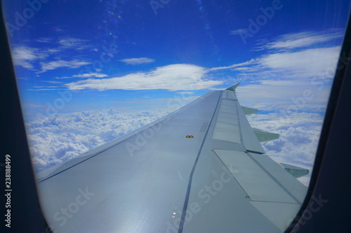 Airplane wing in the sky. View from airplane porthole. Beautiful blue sky with clouds - 238188499