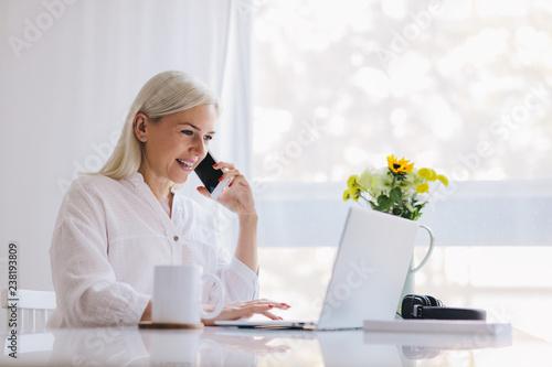 Foto Murales Woman talking on the phone, using laptop.