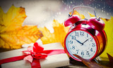 Red vintage alarm clock and gift box with maple leaves on rainy background