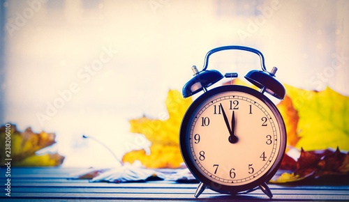 Retro alarm clock and maple leaves with rain drops on window. Autumn season image © Masson
