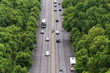 Cyclist waiting in the middle of busy road with cars passing from Brandenburg Gate on several lanes, aerial view with green trees on sides, Tiergarten, Berlin, Germany