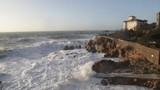 Super slow motion di un oceano in tempesta con onde che si infrangono sugli scogli di fronte a un castello antico. - 238215250