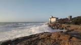Super slow motion di un oceano in tempesta con onde che si infrangono sugli scogli di fronte a un castello antico. - 238215252