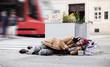 Leinwanddruck Bild - Homeless beggar man lying on the ground outdoors in city asking for money donation.