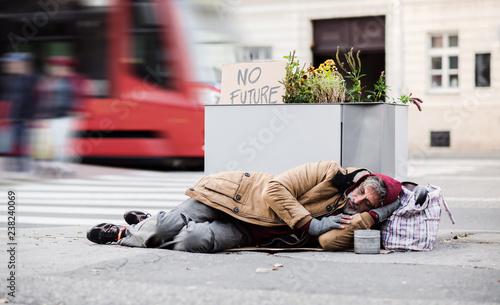 Leinwanddruck Bild Homeless beggar man lying on the ground outdoors in city asking for money donation.