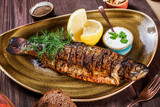 Baked fish with lemon and greens on plate on wooden background. Delicious dish of seafood