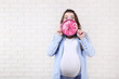Beautiful pregnant woman holding pink clock on brick wall background