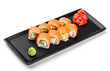 Sushi Roll - Maki Sushi made of salmon, avocado and cream cheese on black plate isolated over white background. Japanese cuisine