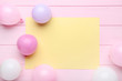 Colorful balloons with sheet of blank paper on pink wooden table