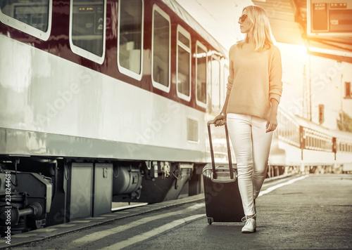 Leinwanddruck Bild Blonde woman with her luggage go near the red train