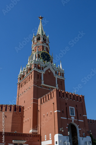 Spasskaya tower of the Moscow Kremlin with clock chimes against the blue sky