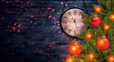 Holiday background with New Year's clock and Christmas wreath. Night view, the arrows on the clock show soon the new year. Rays of night light, glare, neon light on a brick wall background.