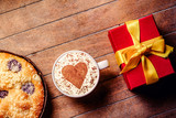 Christmas pie and cup of coffee with heart shape with gift boxes around on wooden table. Hight angle point of view - 238252494