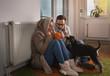 Couple with dog sitting beside radiator and freezing