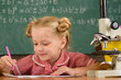 Little child study in science classroom. Elementary school girl work on science project