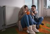 Couple sitting beside radiator and freezing