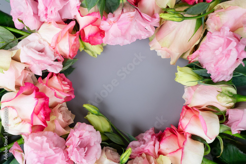 Rose fresh flowers bouquet frame on gray table from above, flat lay scene