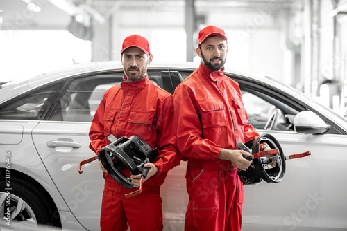 Portrait of two auto mechanics in red uniform standing with disks for wheel alignment at the car service