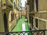 A view along the green canals of Venice, Italy
