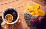 Cup of tea and Christmas box gift with pine cones and Fairy Lights on wooden background - 238271439
