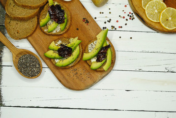 Toast with avocado on a wooden plate and white background
