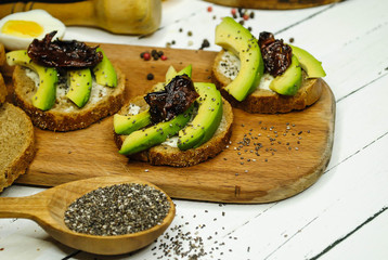 Toasts with avocado, dried pedor and chia on a wooden plate