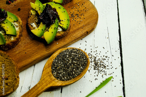 Toasts with avocado, dried pedor and chia on a wooden plate - 238272472