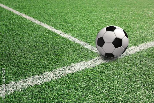 Sunny football ball on soccer field with white lines.