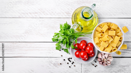 Pasta and ingredients on white wood background: Top view, space for text - 238279097