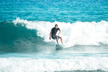 surfer on a shortboard riding a wave in the ocean © Andrei