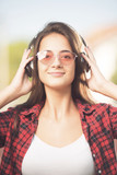 Beautiful teenage girl with sunglasses listening to music