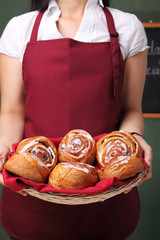 Waitress working at bistro is holding a basket full of sweet buns