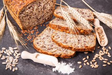 Wholegrain bread for breakfast, ingredients for baking and ears of rye or wheat grain
