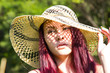 Girl in a straw hat under the bright summer sun