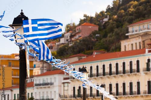Greek flags waving against city buildings
