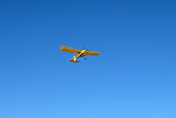 A small yellow airplane ia in the blue sky.