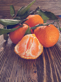 Fresh tangerines with leaves and divided into slices on a wooden background