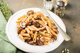 Vegetarian pasta penne with mushroom and pine nuts on kitchen table background. Healthy italian food concept.