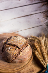 Bread with spikelets of wheat lying on a wooden table