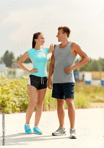 fitness, sport and lifestyle concept - happy couple in sports clothes outdoors