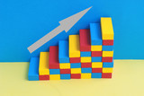 multi colored stairway, formed by toy blocks, arrow pointing up the stairs
