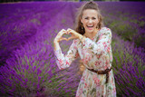 woman at lavender field showing heart shaped hands