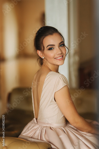 7619bd863d Beautiful stunning young lady in amazing dress sitting on luxury armchair
