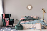 Sun shape like mirror on empty copy space grey wall of contemporary bedroom interior with comfortable bed